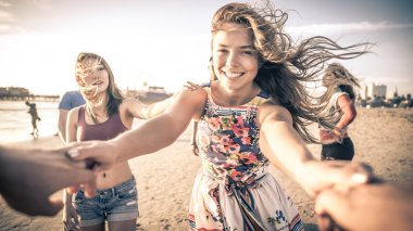 Friends having fun and dancing on beach