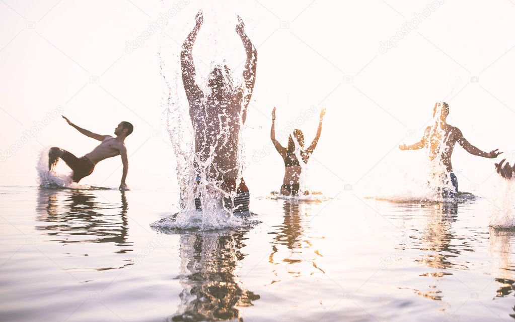 Happy friends splashing water