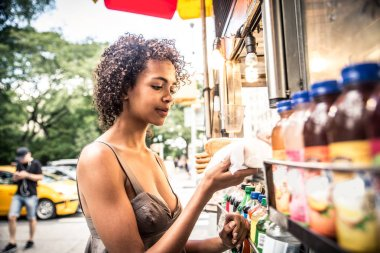 Woman buys hotdog in New York