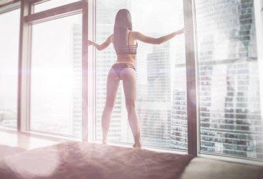 Beautiful woman looking outside the window in her beautiful apar
