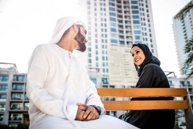 Arabian couple sitting on bench