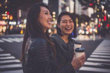 Two japanese women around in Tokyo during daytime. Making shoppi