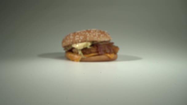 Kamera se pomalu blíží k čerstvě připravenému lahodnému cheeseburgeru. Bílé pozadí