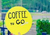nápis káva jít na žlutou kulatou plaketu na ulici.