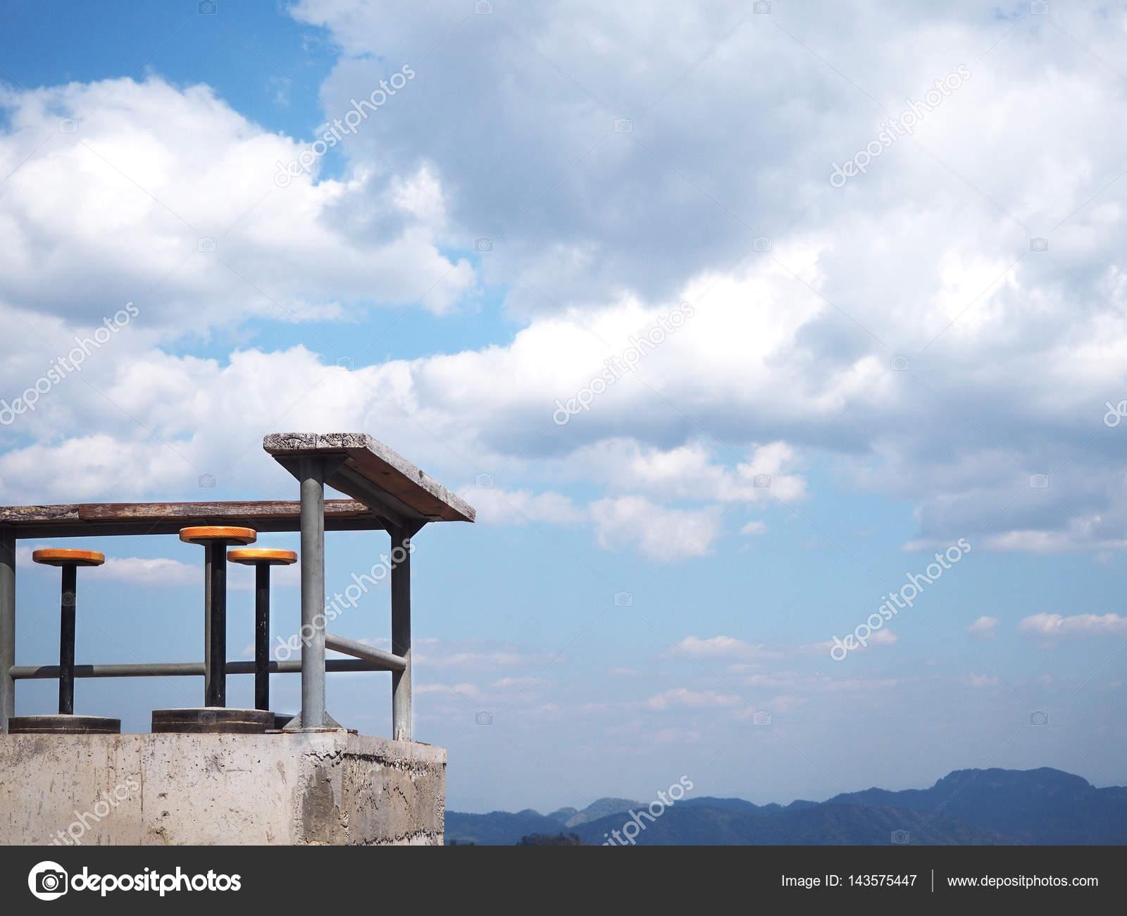 Angolo di sgabelli per esterni e tavoli contro cielo blu con