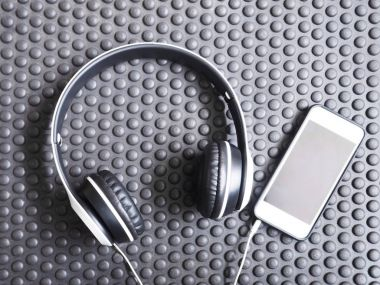 Headphone and mobile phone on black rubber mat background