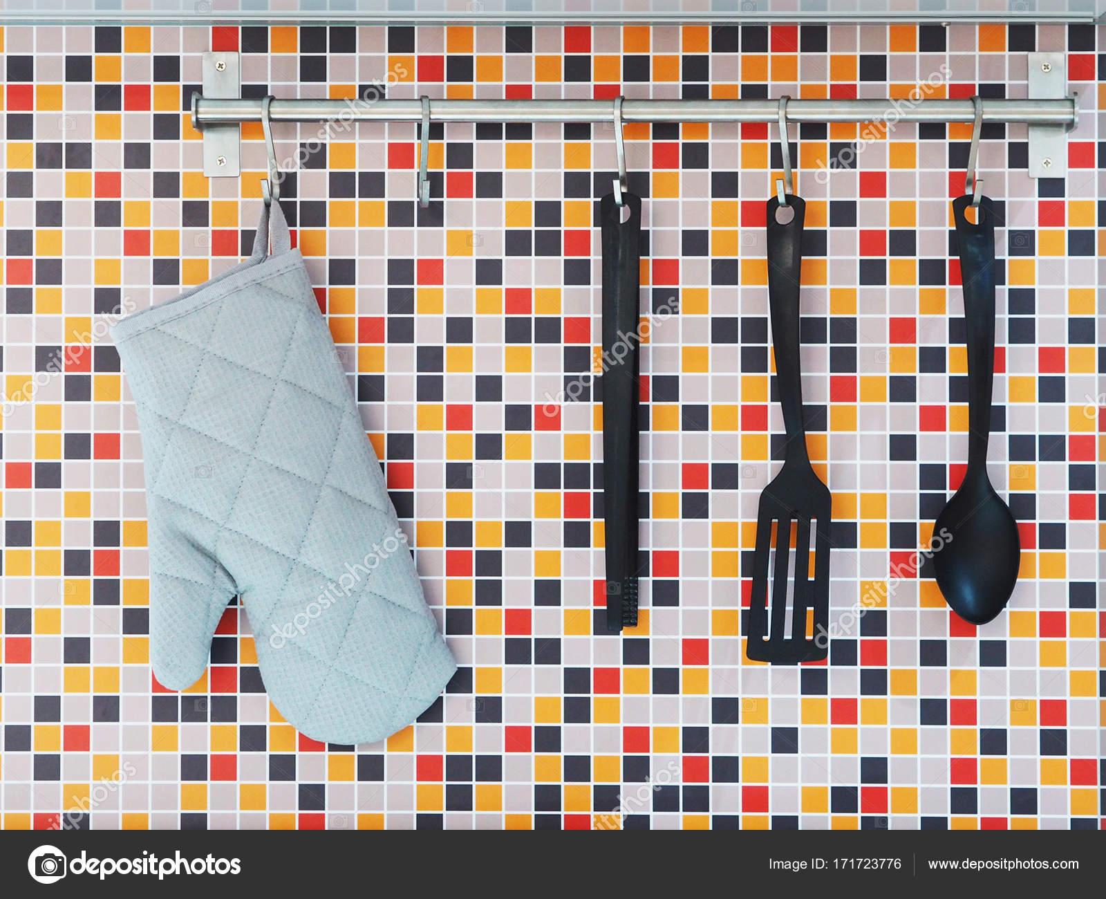 Utensili da cucina appeso sopra colorato mosaico piastrelle di