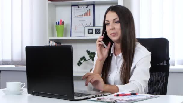 A lány az irodában, beszél a mobiltelefon