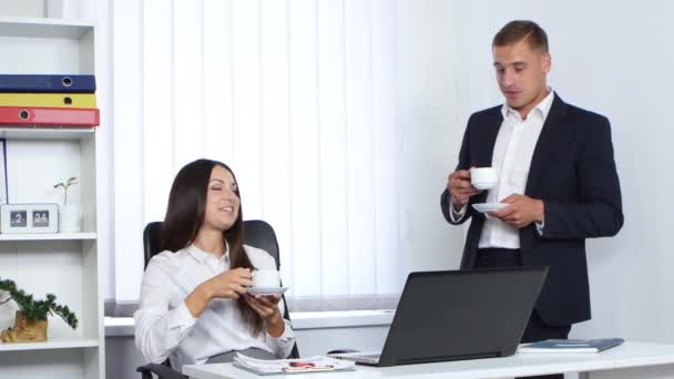 Colleagues at work drinking coffee and talking