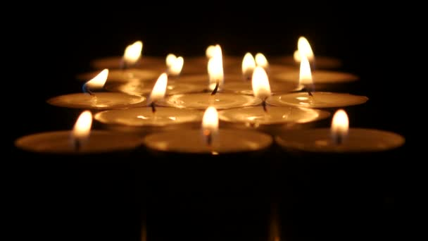 Small candles burning on a dark background. Close up