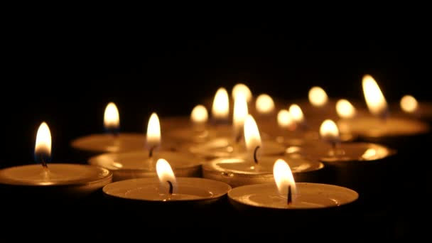 Many burning small candles on dark background. Close up