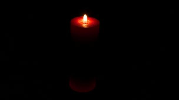 Plamen svíce izolované na černém pozadí. Červená svíčka. Detailní záběr