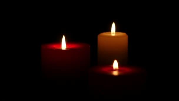 Tři svíčky na tmavém pozadí. Zblízka. Zpomalený pohyb
