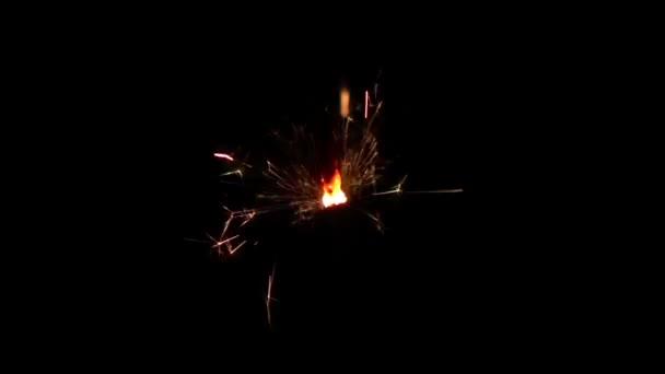 Wunderkerze brennt über schwarzem Hintergrund. Zeitlupe