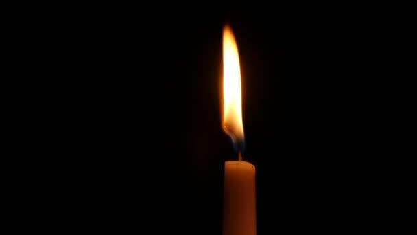 Hořící svíčka, izolované na černém pozadí. Detailní záběr
