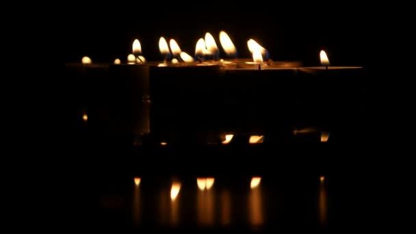 Skupina zapálených malých svíček na černém pozadí. Detailní záběr