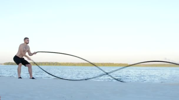 Training with ropes on a sandy bank near the water