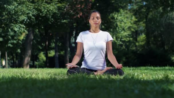 Holka dělá jógu v parku a poslech hudby ve sluchátkách