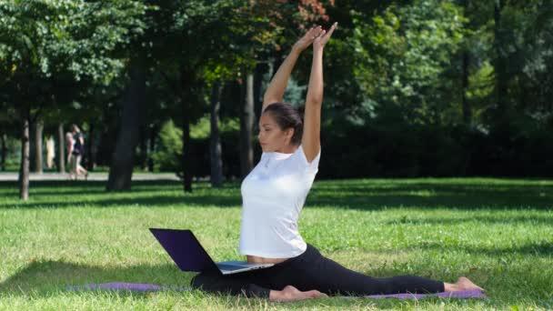 Dívka má praxi jógy v parku s notebookem