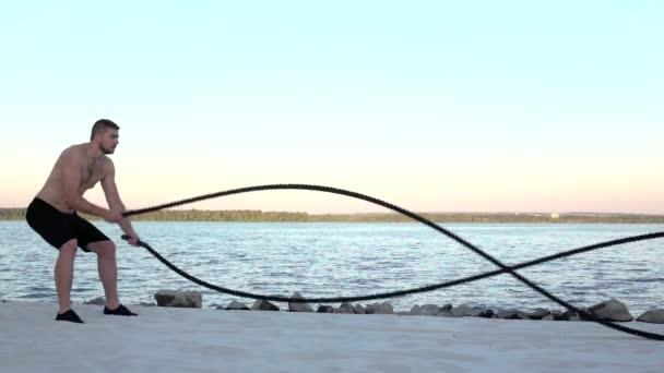 Sportler trainiert mit den Seilen am sandigen Ufer. Zeitlupe