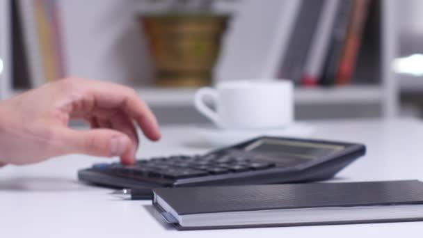 Muž s blueprint počítat na kalkulačce a zápis do zápisníku. Detailní záběr