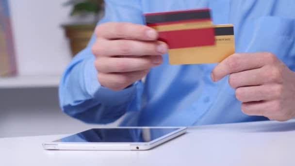 Mann kauft online mit digitalem Tablet und goldener Kreditkarte ein. Online-Shopping. Nahaufnahme