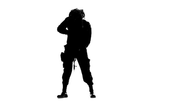 Man points the gun down and to the sides. Silhouette