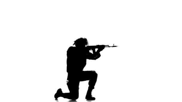 Soldier stands on one knee and taking aim at the distance. Silhouette