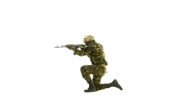 Soldier took aim, while standing on one knee. White backgraund