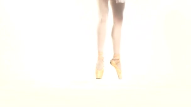 Young ballerina dancing, closeup on legs and shoes, standing in pointe position. Slow motion