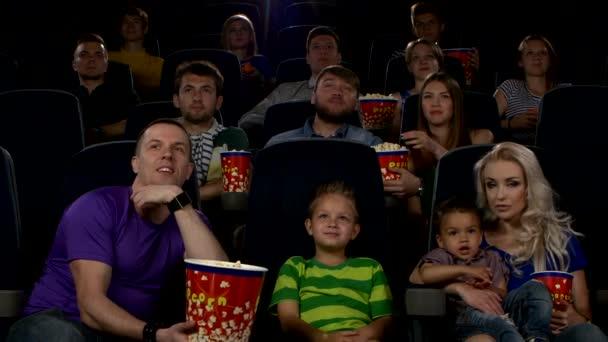 junge Leute, die im Kinosaal sitzen. Familie in der ersten Reihe
