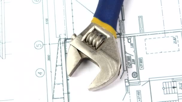Adjustable wrench on building plan, scheme, rotation, close up