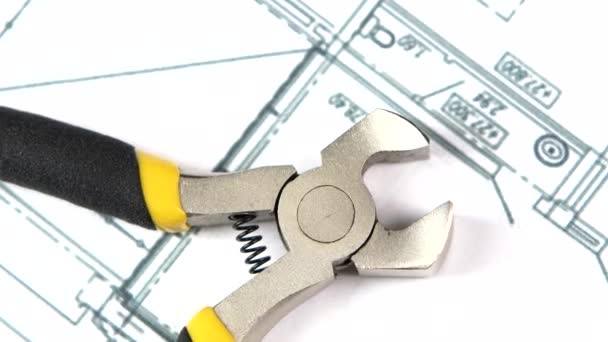 Wire cutters with yellow, gray handle on building plan, scheme, rotation, close up