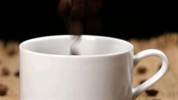 Pörkölt babkávé esés-ba egy fehér kupa. Lassú mozgás