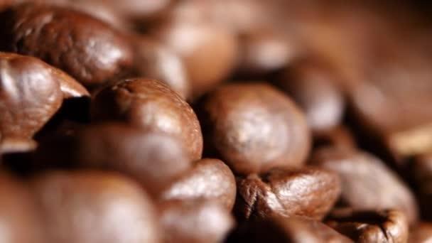 Velké haldy voňavé pečené hnědá kávová zrna. Otáčení. Detailní záběr