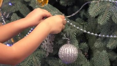 Little girl carefully decorating christmas tree before new years eve
