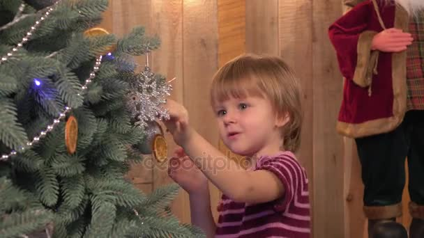 Little girl decorating Christmas tree before new years eve.,wooden background