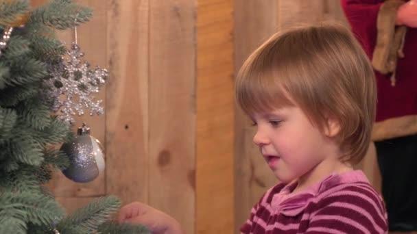 Kleines Mädchen in der Nähe von Christbaum, Urlaub, grüne Neujahrsecken, hölzerner Hintergrund