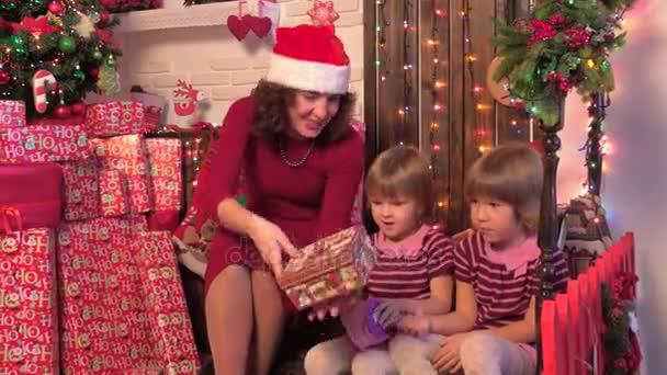 Boldog család közelében egy karácsonyfa, anya, gyerekek, bemutatja, fából készült háttér