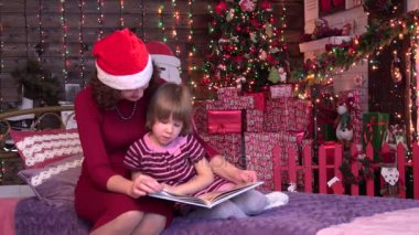Mother and her daughter reading in bed Christmas Background