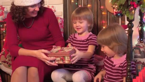 Moeder met twins uitpakken presenteert onder de kerstboom kerst