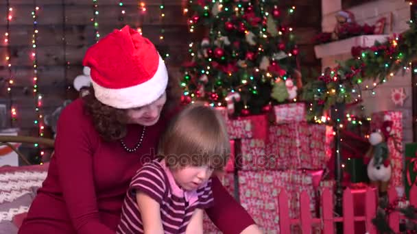 Charming mother is showing images in a book to her cute little daughter on christmas background
