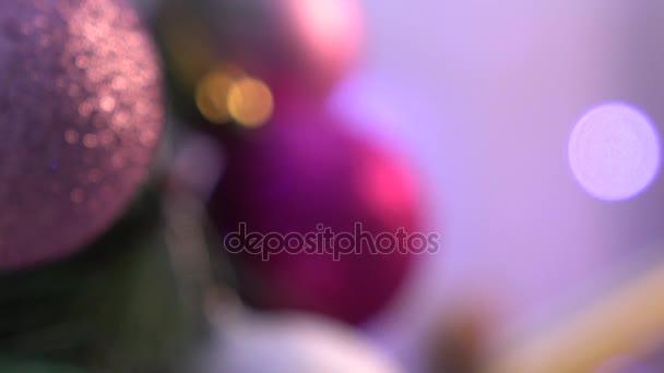 Violet christmas decoration on violet background, ligh playing, dynamic change of focus