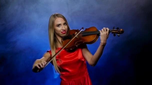 Girl blonde plays the violin professional. Smoky background. Slow motion