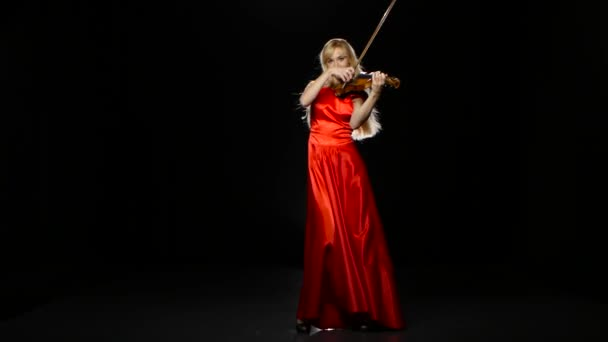 Woman plays the fiddle. Studio. Black background