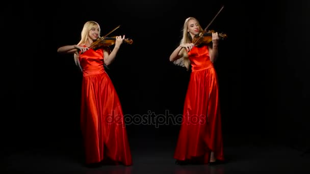 Two women playing the viola. Studio. Black background