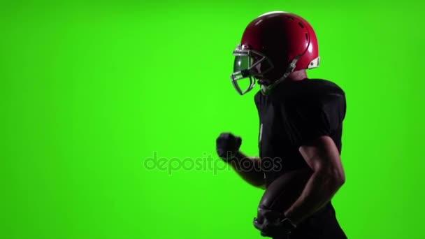 Futás-val a labdát és egy piros sisak labdarúgó. Lassú mozgás