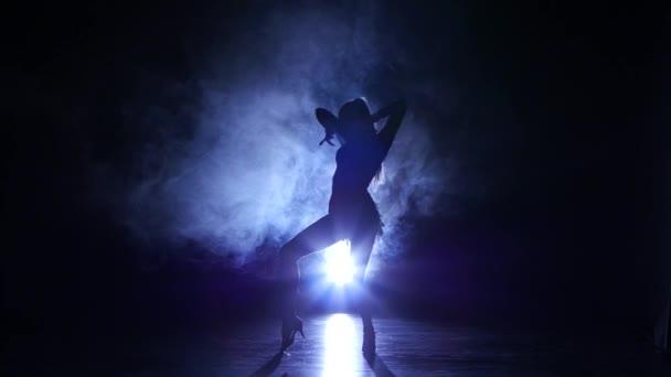 Woman dancing rumba in studio, silhouette. Dark background, blue backlight