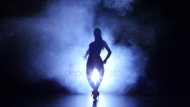 Woman dancing samba in studio, silhouette. Dark background, blue backlight