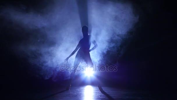 Nő tánc cha-cha-cha stúdió, silhouette. Sötét háttér, kék háttérvilágítás